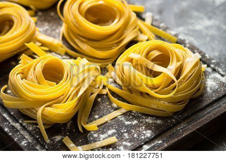 Fresh italian raw homemade pasta tagliatelle at wooden table. Close up