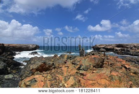 Rusty jagged rocks in front of Aruba's black sand beach.