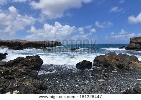 Waves rolling ashore on Aruba's black sand stone beach.