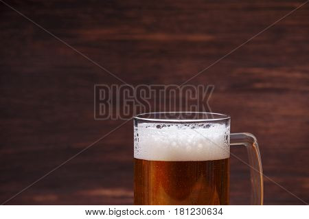 Glass of beer with foam. Mug or pint of ale. Alcohol drink. Pub or bar concept. On rustic wooden background.
