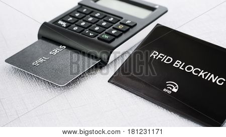 Black colour RFID protection sleeve for secure credit card from hacking in front and TAN generator with credit card in it on middle ground