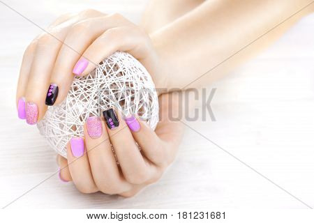 purple manicure with a white ball of yarn on the white wooden table.