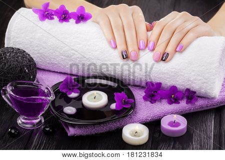 beautiful purple manicure with violet, candle and towel on the black wooden table. spa