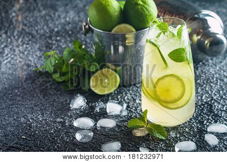 Mojito cocktail with lime and mint in highball glass on dark stone background