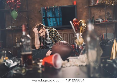 Bearded Young Man With Hangover Sitting On Couch In Messy Room After Party