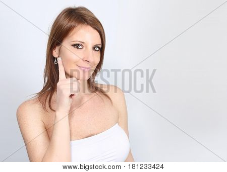 Beautiful woman applying an anti wrinkle cream on her face on a white background