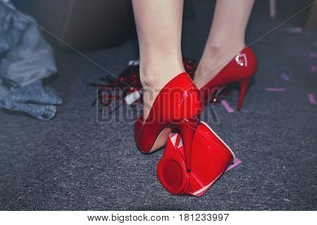 Low Section Of Woman's Legs In Red Heels In Messy Room After Party