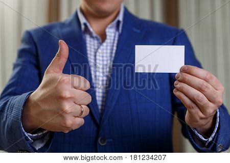 Businessman holding visit card. Man showing blank business card. Person in blue suit showing thumb up. Mock up design.