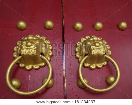 Taipei Taiwan - October 20 2016: Golden door knocker in a shape of a lion's head on a red wooden door
