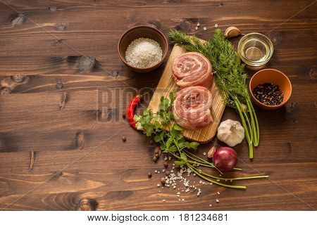 raw breast wrapped in a roll with ingredients for cooking meat.