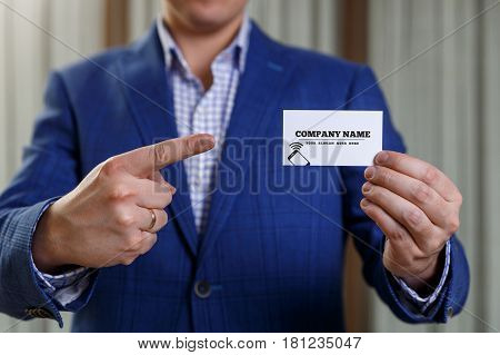 Businessman holding visit card. Man showing blank business card with phone icon. Person in blue suit points a finger. Mock up design.