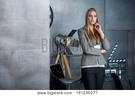 Young businesswoman standing in studio, looking at camera.