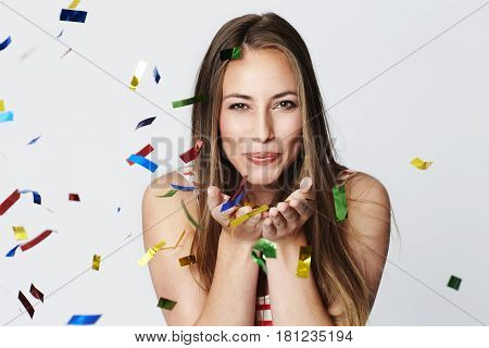 Confetti woman blowing at camera portrait studio shot