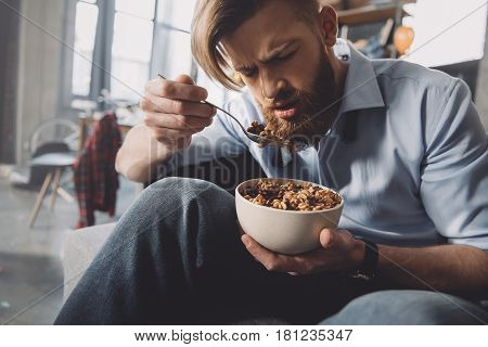 Man Eating Corn Flakes In Messy Room After Party