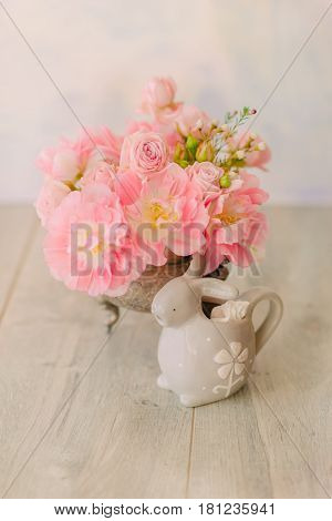 A bouquet of pink decorative tulips in an antique silver vase and a porcelain rabbit
