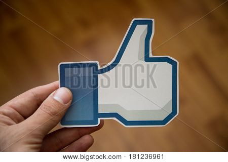 Man holding facebook like button printed on paper