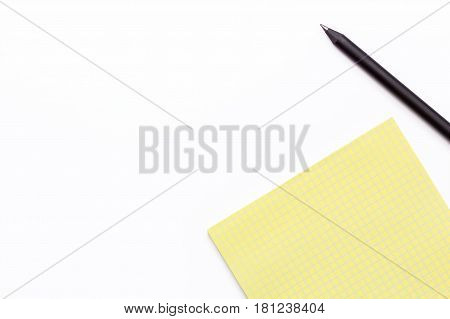 yellow notebook and black pencil on a white background. Minimal business concept. Top view. Flay lay.
