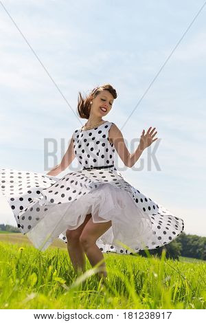 pretty Rockabilly Girl with a petticoat dress is dancing rock & roll on the meadow