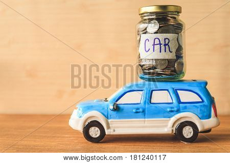 Coins in glass jar with car label and car toy on wooden table. Financial Concept