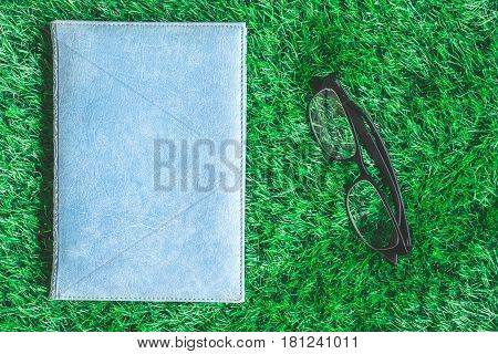 Top view of Blue hardback book with glasses on green grass background.