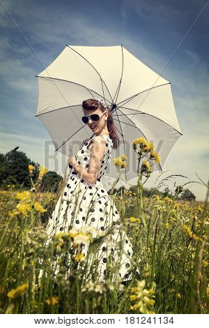 Retro vintage filtered picture with a pretty 50´s Girl in a wildflower meadow