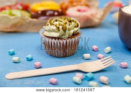 Cupcakes with buttercream and donuts. Fork with marshmallows. Sweet dessert cakes. On wooden table.