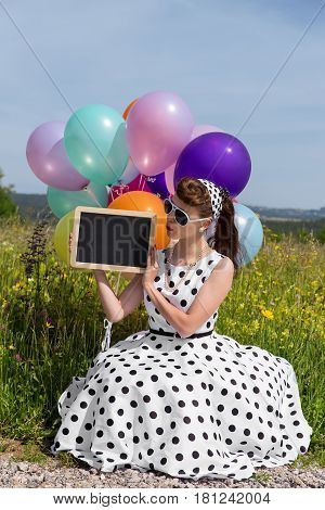 young pretty woman with a white vintage petticoat dress from the 50´s holding a board with copyspace