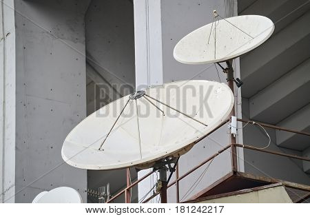 Closeup of several parabolic antennas mounted on a residential building