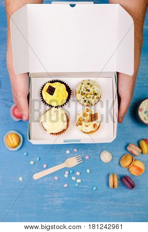Cupcakes and macaroons. Male hands holding delivery box. Cakes with buttercream. Almond macaron cookies. Sweet dessert.
