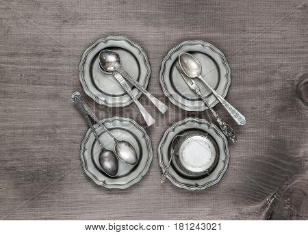 Antique silver cutlery on four vintage tin plates on old wooden background