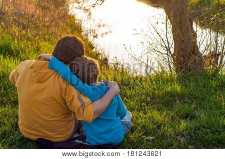 Father and son are hugging at the pond
