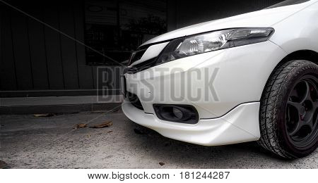 White car bumper and lamp side view parking at office photo high light only red color on the street have dry leaf.