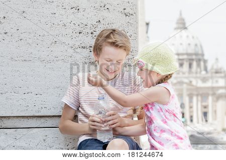 Two siblings are soaking each other drinking water from plastic bottle in hot summer day
