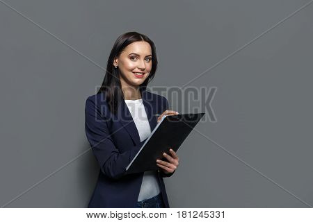 Busy elegant business woman in formal suit writing down notes to notepad while standing on gray studio background. Concentrated female office worker planning working schedule with notebook, copy space