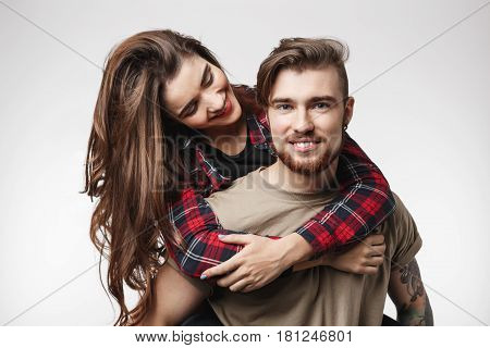 Closeup of bearded man looking straight, girl sitting on man's back, hugging looking with smile.