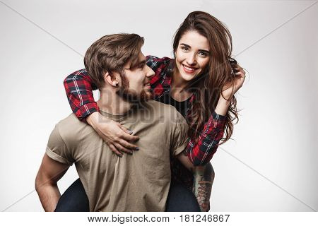 Woman sitting on man's back, looking at camera. Man looking at woman touching her hair.