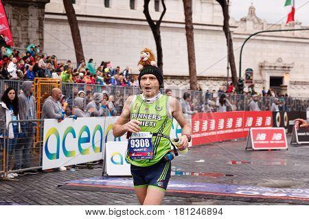 Rome Italy - April 2 2017: An athlete taking part in the 23rd Rome marathon reaches the finish line on Via dei Fori Imperiali.