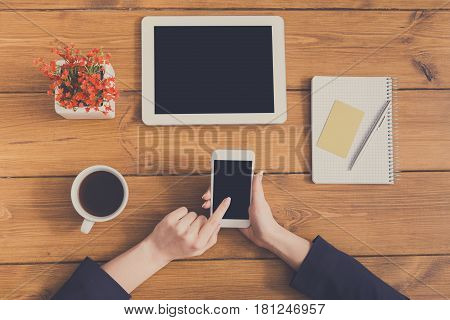 Top view table of business woman checking schedule and touching screen on phone. Freelancer working with portable computer while sitting at wooden desk at coffee shop