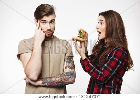 Tired man looking at camera, funny woman annoying man, playing with burger, making noise.