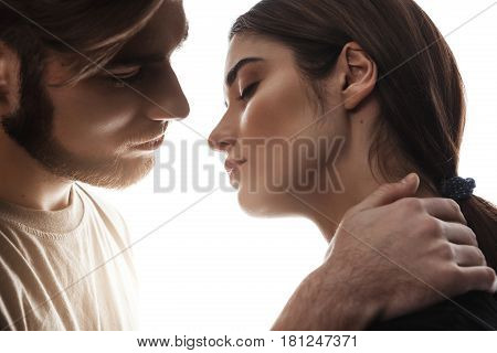 Man holding hand on woman's neck. Eyes closed. Soft kiss. Beautiful couple about to kiss.