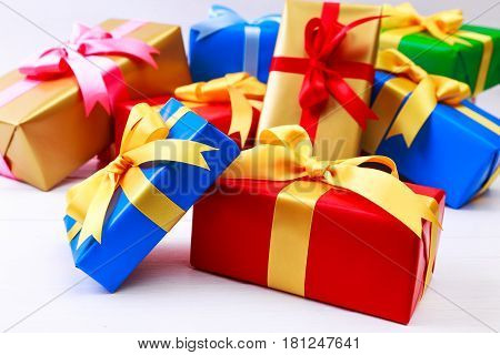 Gift boxes with bow. Colored presents wrapped with paper and ribbons. Christmas or birthday packages. Celebration design. On white table.