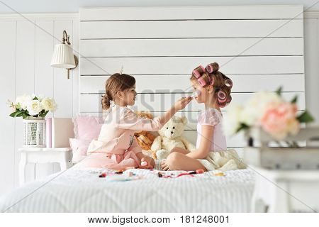 Two beautiful girls are sitting on the bed in a fancy bedroom. They are doing make up. hildhood, innocence, purity oncept