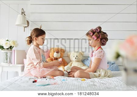 Two pretty well-dressed girls are sitting in a bedroom. Due to the mimic of one of them she is offended by the another.