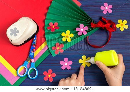 Making gift for Mother's Day by the child. Colorful bouquet of flowers out of paper. Children's art project. DIY concept. Step-by-step photo instruction. Step 6. Child glues flowers on a fan