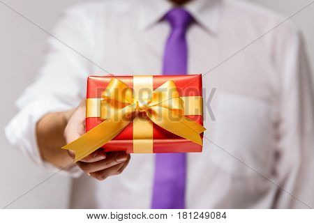 Male hand holding a gift box. Present wrapped with ribbon and bow. Christmas or birthday red package. Man in white shirt and necktie.