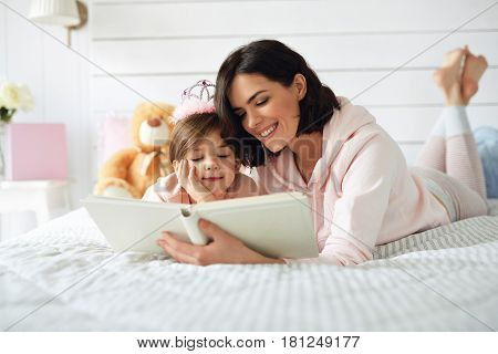 There are mother and daughter laying on a bed. They are reading a book. Girl is wearing plush crown and listening to her mother patiently