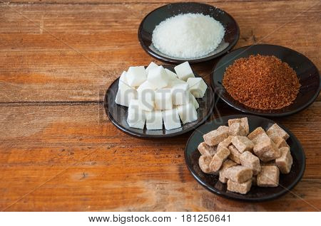 Variety Of Brown (cane) And White Sugar. Granulated And Lump Sugar In A Black Small Plates On A Wood
