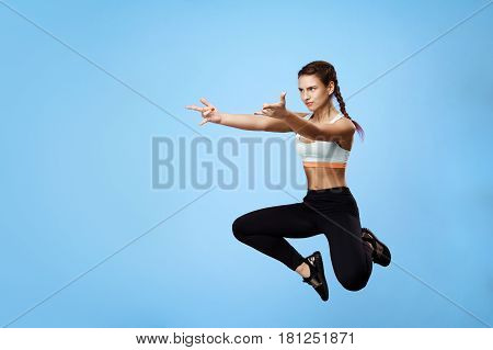 Woman in cool sport look making fun, jumping with raised hands while training