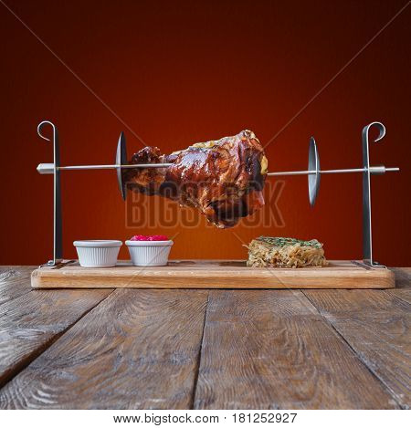 Grill meat dish, roasted pork knuckle on spit with fried sauerkraut cabbage and sauces. Juicy meat meal, german food on red background