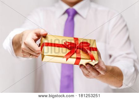 Male hands holding a gift box. Present wrapped with ribbon and bow. Christmas or birthday package. Man in white shirt and necktie.
